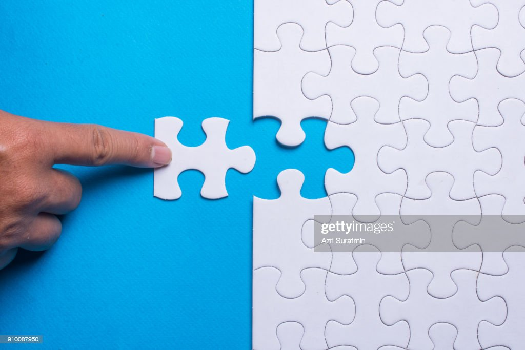 Hand holding piece of white puzzle on blue background. Business and team work concept. : Stock Photo