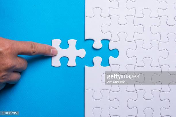 hand holding piece of white puzzle on blue background. business and team work concept. - raadsel stockfoto's en -beelden