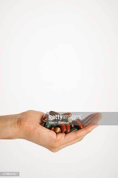 Hand holding pile of pills