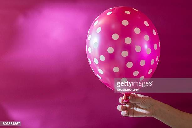Hand holding pink balloon with white polka dots