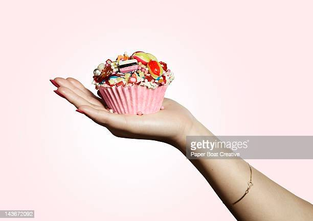 hand holding pink designed cupcake full of sweets - indulgence stock pictures, royalty-free photos & images