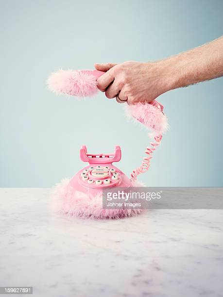 Hand holding pink furry telephone