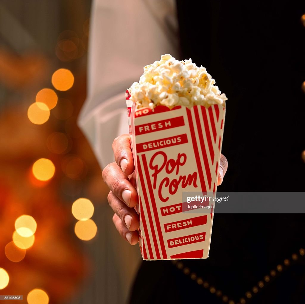Hand holding popcorn : Stock Photo
