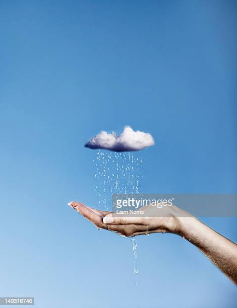 hand holding pouring rain cloud - water conservation stock pictures, royalty-free photos & images
