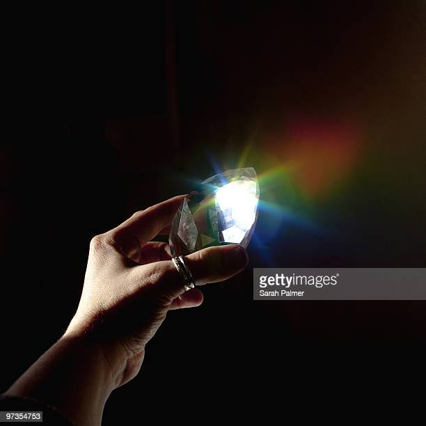 hand holding prism refracting rainbow light