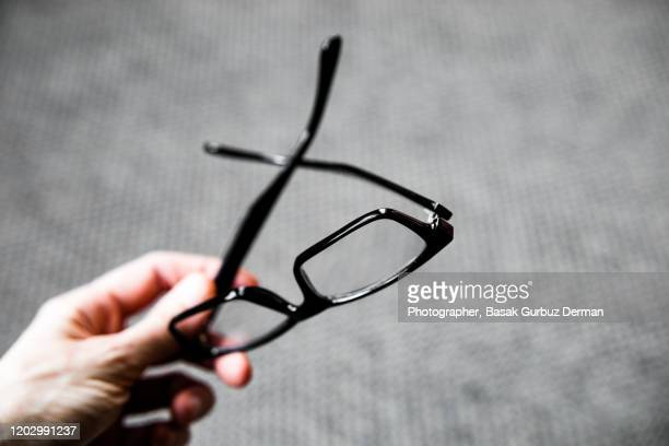 a hand holding reading glasses - reading glasses stock pictures, royalty-free photos & images