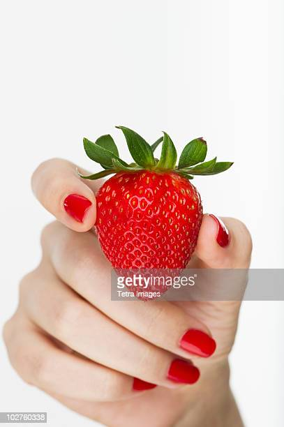Hand holding red strawberry