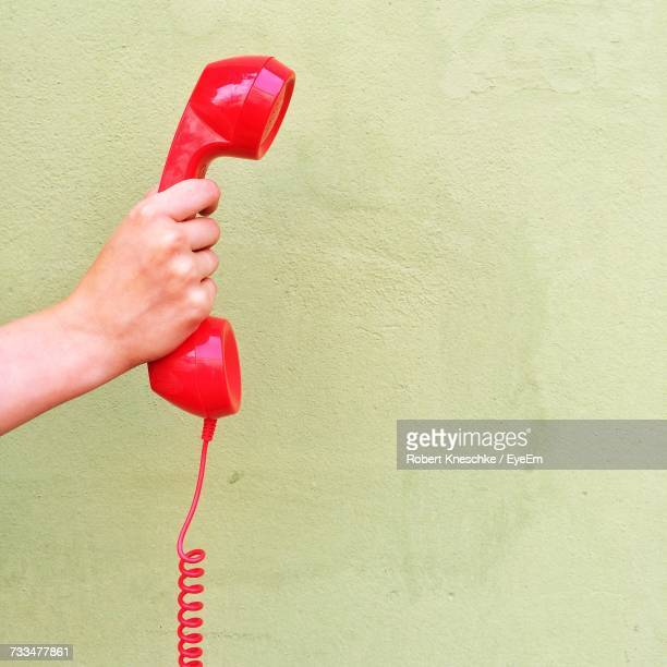 Hand Holding Red Telephone Receiver Against Wall
