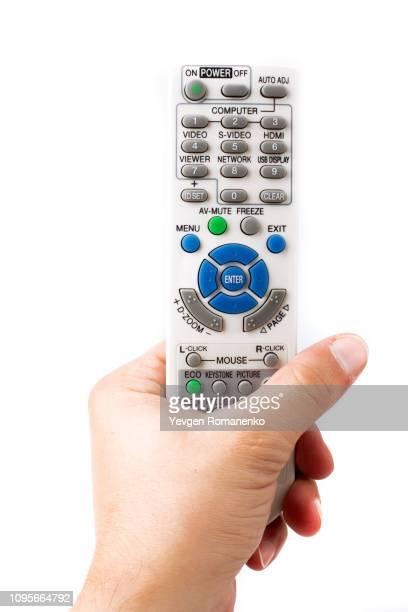 hand holding remote control on white background - controllato a distanza foto e immagini stock