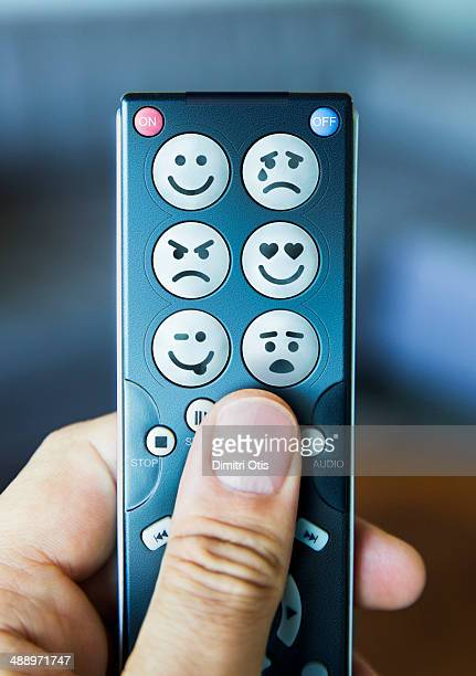 Hand holding remote control with emoticon buttons