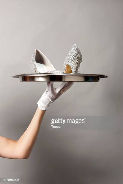 Hand holding rhinestone shoes on silver platter
