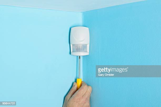 Hand holding screwdriver to base motion sensor in corner of blue wall