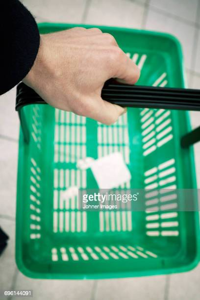 Hand holding shopping basket