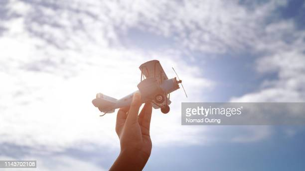hand holding small aircraft.startup business flying and moving to freedom concept. - free business coaching stock pictures, royalty-free photos & images