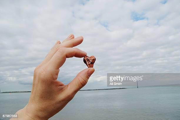 Hand holding small heart-shaped stone