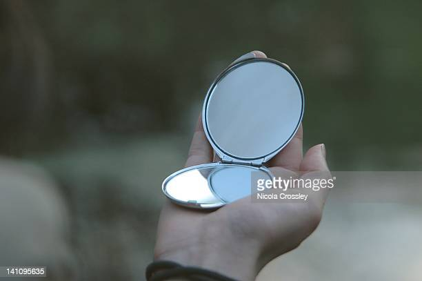 Hand holding small silver mirror
