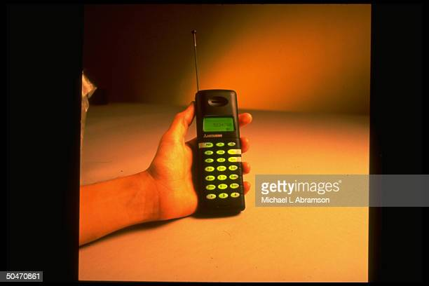 Hand holding smallest cellular phone on market made by Mitsubishi