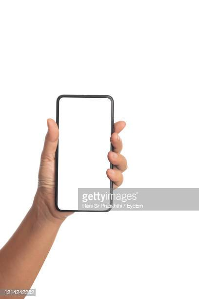 hand holding smart phone over white background - human hand stock pictures, royalty-free photos & images