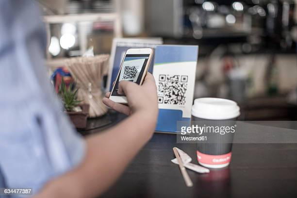 Hand holding smart phone, scanning barcode