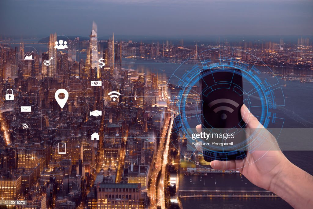 Hand holding smart phone, wireless technology communication network on city background : Stockfoto