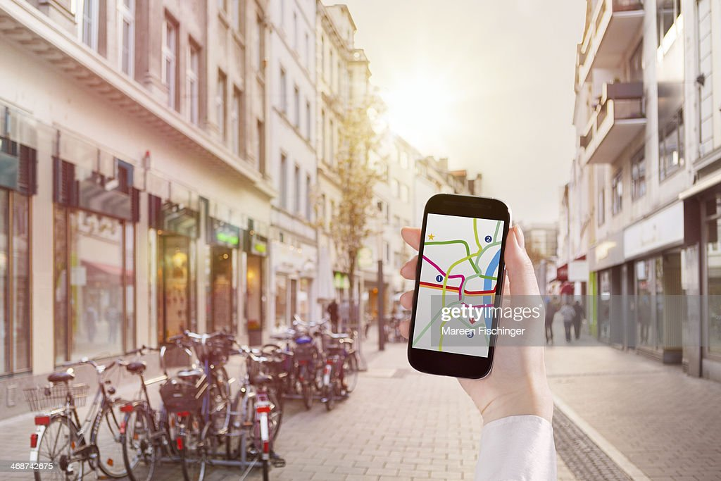 Hand holding smart phone with map app in city : Stock-Foto