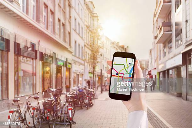 hand holding smart phone with map app in city - mid adult men stock pictures, royalty-free photos & images
