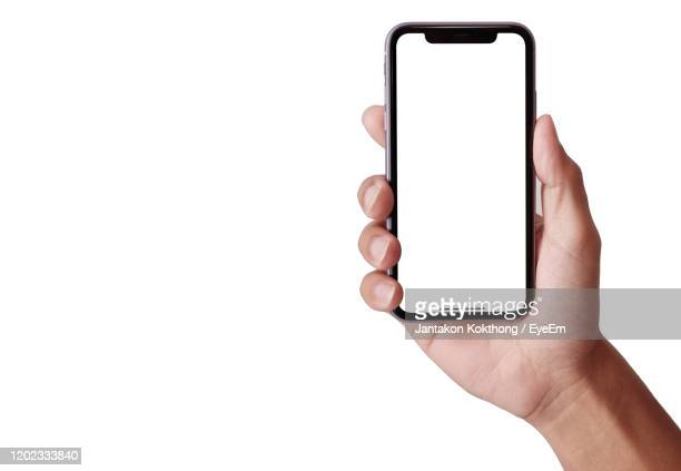 hand holding smartphone iphone 11 - human hand stock pictures, royalty-free photos & images