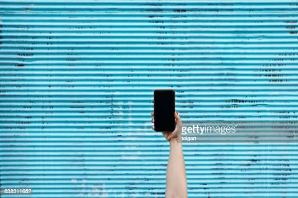 スマートフォンを持つ手 - 建具 シャッター ストックフォトと画像