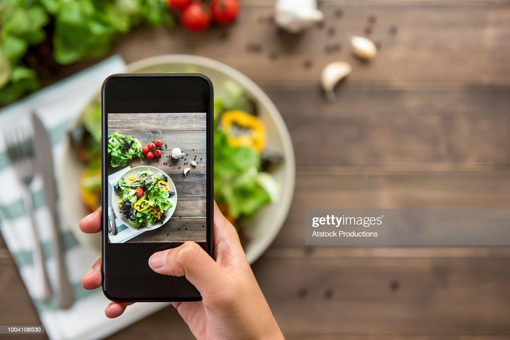 Hand holding smartphone taking photo of beautiful food, mix fresh green salad : Stock Photo