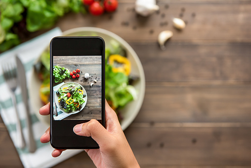 Hand holding smartphone taking photo of beautiful food, mix fresh green salad 1004108530