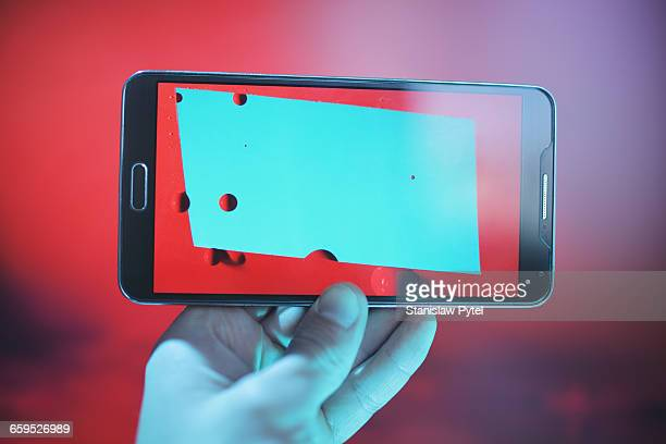 Hand holding smartphone with abstract image