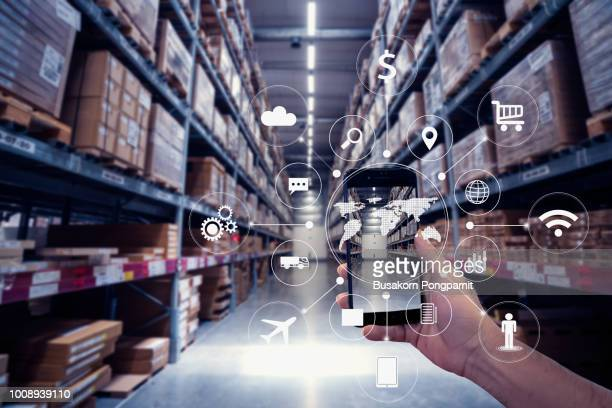 hand holding smartphone with AR application for check order pick time in smart factory warehouse, technology interface global partner connection for Logistic Import Export background