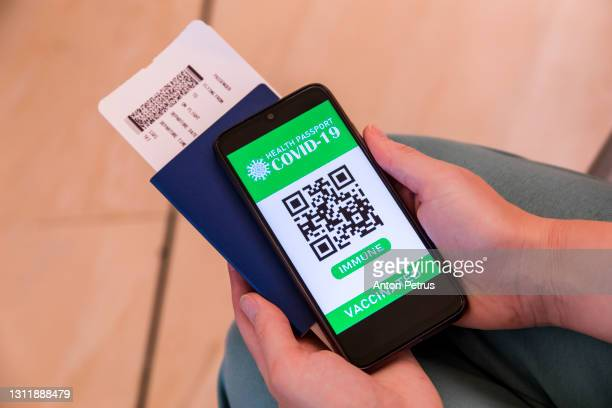 hand holding smartphone with digital vaccination passport. health passport with certificate of covid-19 vaccination - certificate stock pictures, royalty-free photos & images