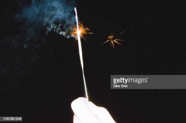 hand holding sparkler against black background - briel stock pictures, royalty-free photos & images