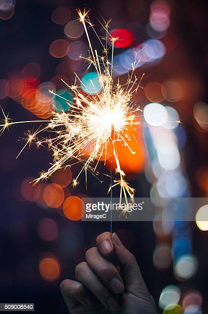 Hand Holding Sparkler before Colorful Bokeh