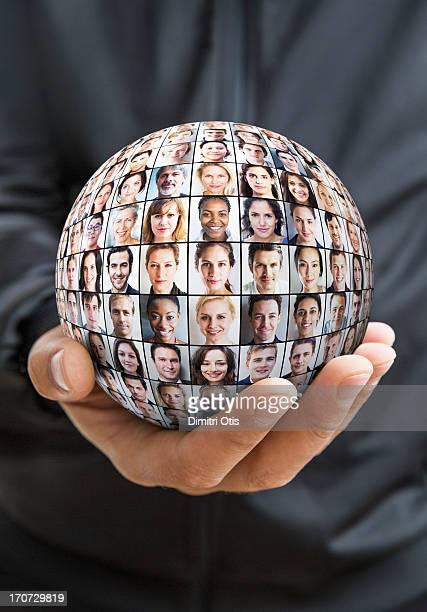 Hand holding sphere with grid of many faces
