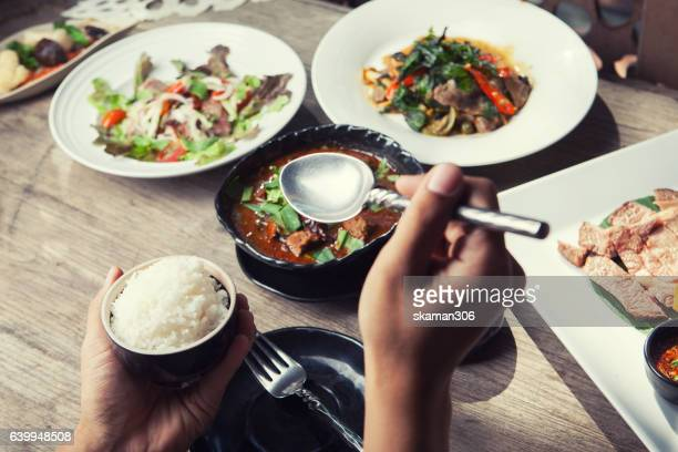 hand holding spoon and dinner with thailand food hot and spicy with herb on wooden table - curry soup fotografías e imágenes de stock