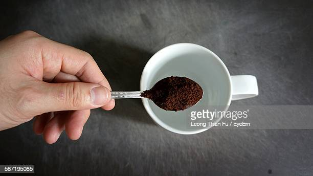 hand holding spoon of coffee powder over cup - ground coffee stock photos and pictures