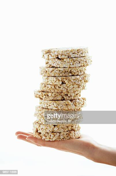 Hand holding stack of rice cake against white background.