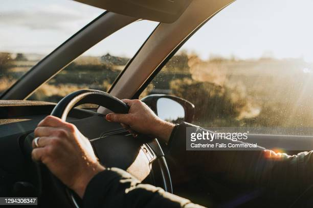 hand holding steering wheel in a car - car stock pictures, royalty-free photos & images