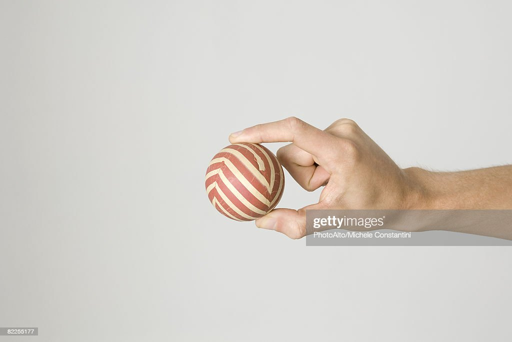 Hand holding striped ball : Stock Photo