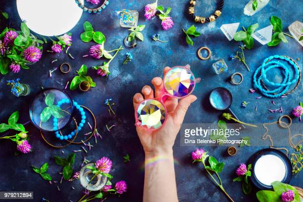 Hand holding stylish pink kaleidoscope sunglasses with gold bracelets and rings in a feminine style concept with clover flowers on a dark background. Beautiful summer accessories.