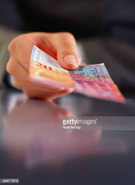Hand Holding Swiss Francs
