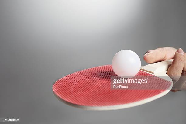 Hand holding table tennis paddle&ball