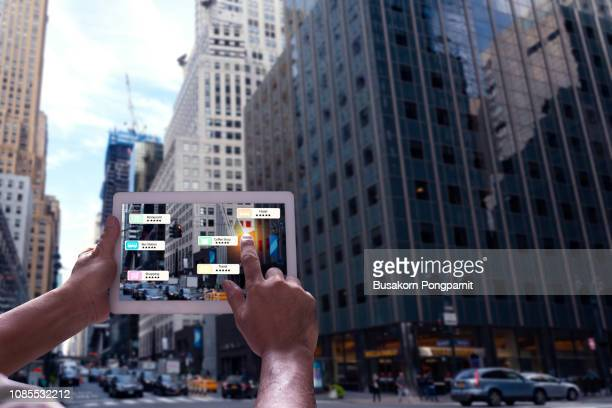 hand holding tablet use ar application to check relevant information about the spaces around customer. new york city in background. - realtà aumentata foto e immagini stock
