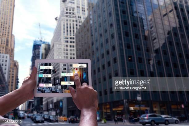 hand holding tablet use ar application to check relevant information about the spaces around customer. new york city in background. - erweiterte realität stock-fotos und bilder