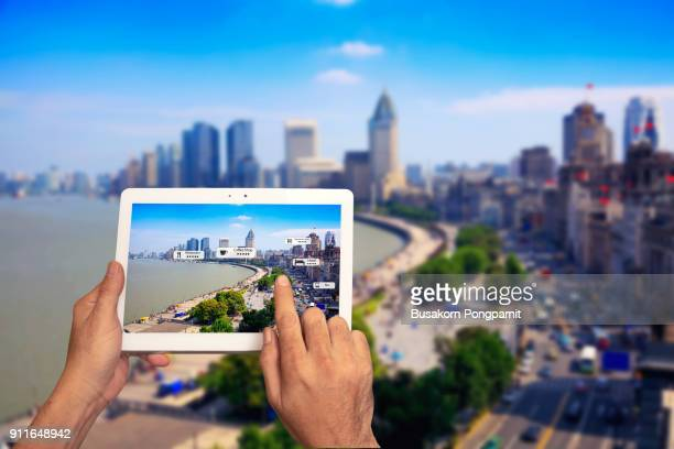 hand holding tablet use ar application to check relevant information. shanghai china in marketing street background concept - marketing icons stock photos and pictures