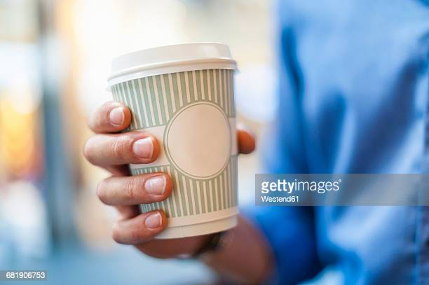 Hand holding takeaway coffee