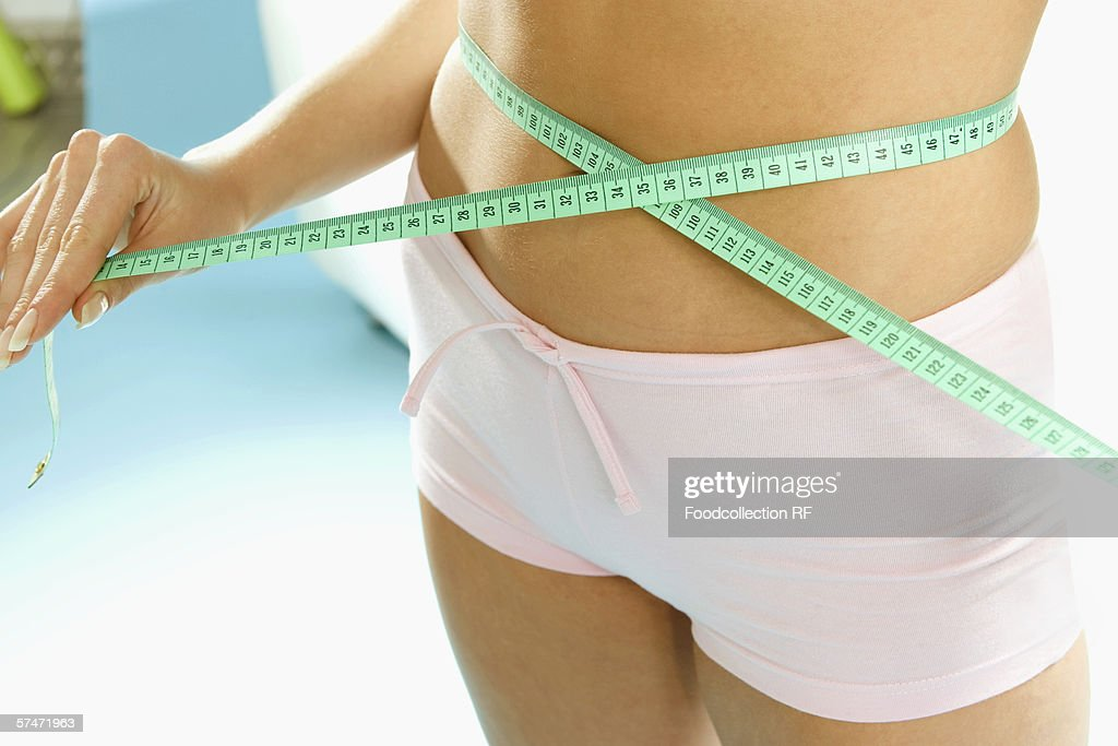 Hand holding tape measure around waist (detail) : Stock Photo