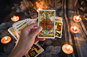 Hand holding tarot card with candlelight on the darkness background for Astrology Occult Magic illustration - Magic Spiritual Horoscopes and Palm reading fortune teller concept